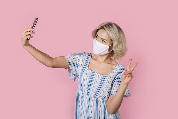 Adorável senhora loira com máscara médica gesticulando com o símbolo da paz enquanto tira uma selfie na parede rosa