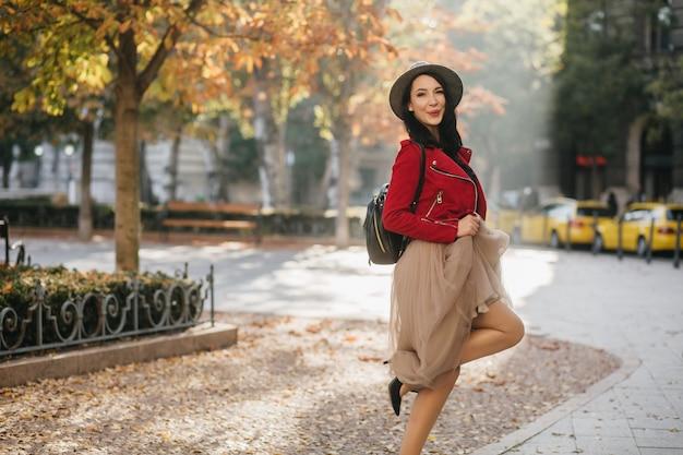 Adorável senhora morena de saia longa dançando no parque outono