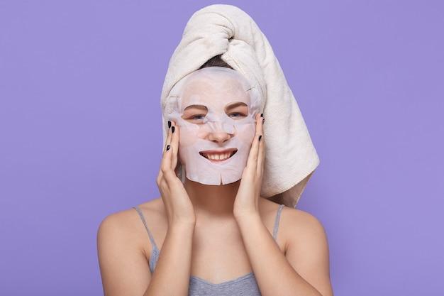 Adorável senhora sorridente enrolada em toalha posando isolada em lilás, usando máscara de tecido para procedimentos de beleza