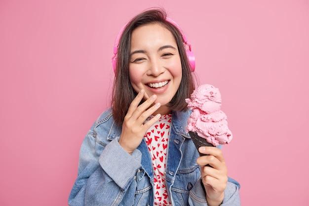 Adorável sorridente mulher asiática tem cabelo escuro aproveita o tempo livre durante o dia de verão segura delicioso sorvete em waffle preto ouve música em fones de ouvido sem fio usa roupas jeans isoladas em rosa
