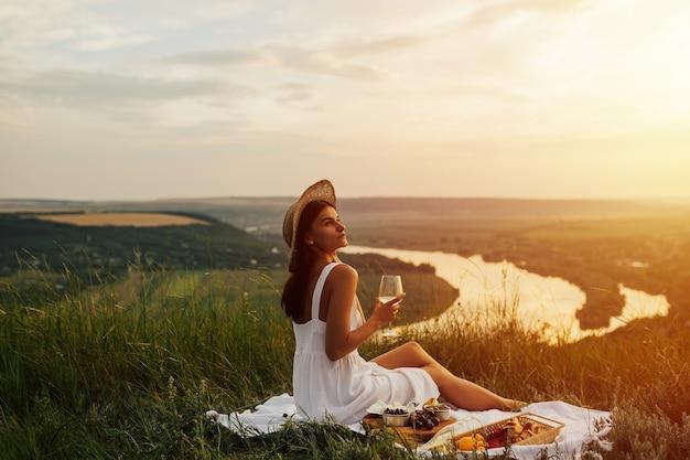 Adorável tenra garota vestida de branco com chapéu de palha, fazendo um piquenique no pôr do sol de verão na montanha.