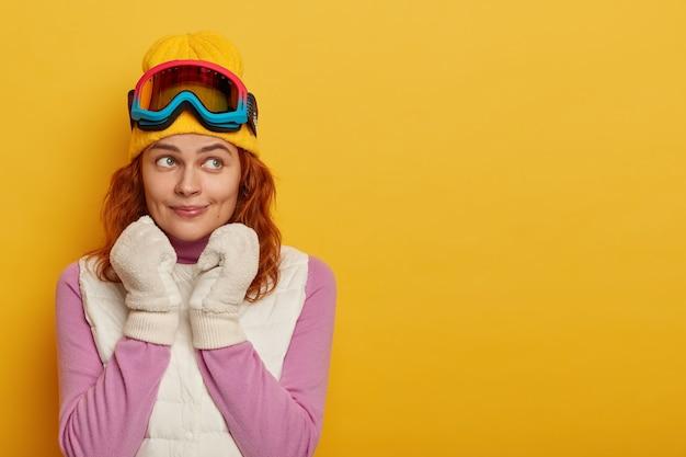 Adorável turista feminina tem cabelo ruivo, usa chapéu amarelo com óculos de esqui na cabeça, luvas brancas macias, macacão roxo com colete branco, tem descanso ativo durante o tempo de neve, olha para longe, posa dentro de casa
