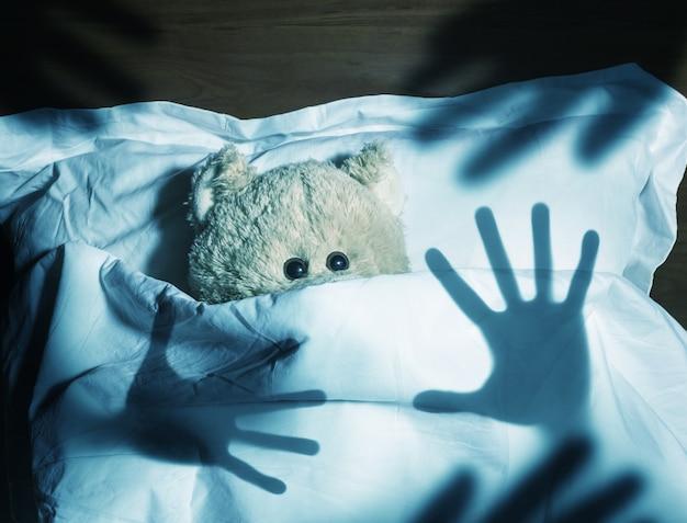 Adorável ursinho de pelúcia deitado na cama, assustado
