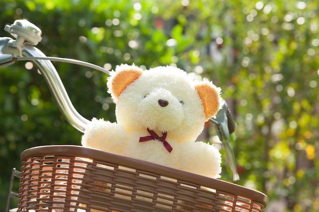 Adorável ursinho em bicicleta de cesta. de manhã