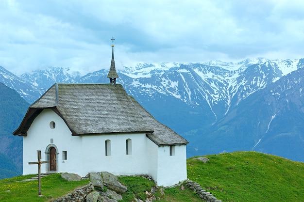 Adorável velha igreja de montanha na vila de bettmeralp (suíça). visão nublada de verão.