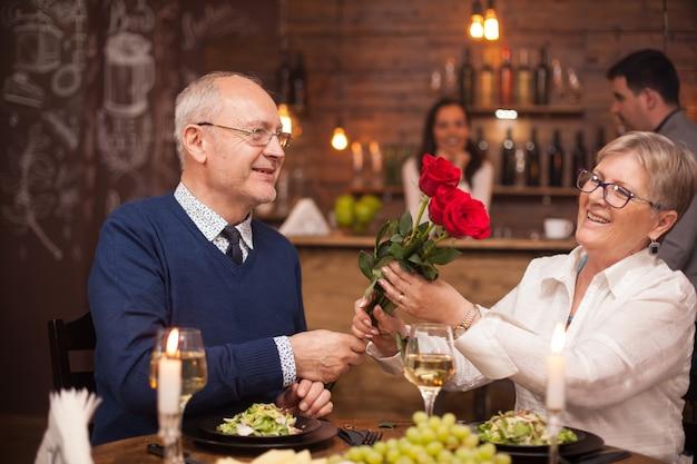 Adorável velhinha admirando as flores que seu marido lhe deu. casal na casa dos sessenta anos jantando. uvas frescas. copo de vinho.