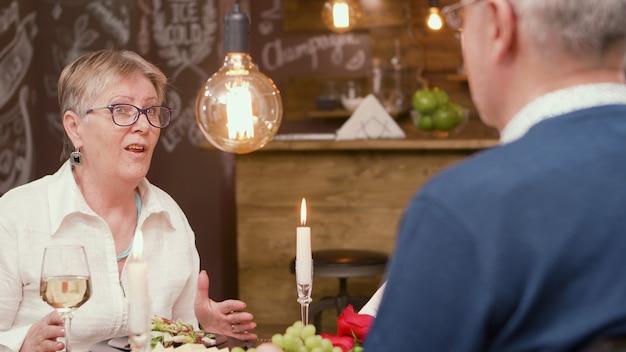 Adorável velhinha contando uma história interessante para o marido durante a hora do almoço. casal de idosos. homem e mulher na casa dos sessenta.