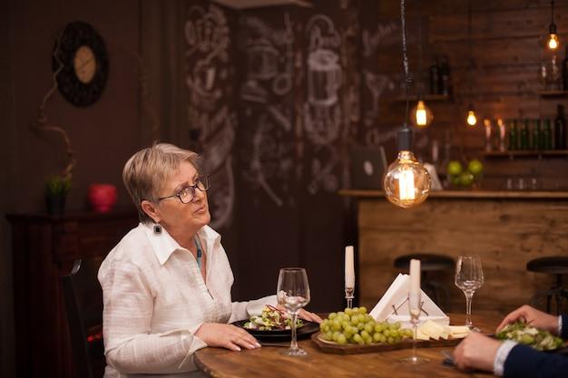 Adorável velhinha conversando com o marido enquanto jantava em um restaurante vintage. feliz casal de velhos.