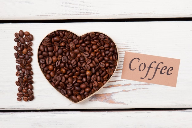 Adoro café fresco da manhã. os grãos de café torrados em forma de coração formam uma camada plana. superfície de madeira branca.
