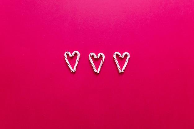 Adoro composição. cartão de dia dos namorados. bastão de doces de três corações em um fundo vermelho