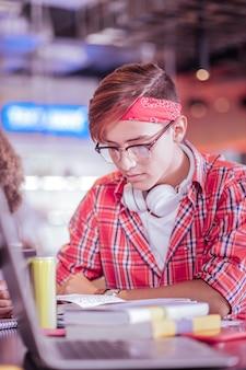 Adoro estudar. garoto loiro bonito curvando a cabeça enquanto lê um livro