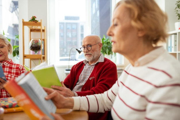 Adoro ler. agradável homem idoso segurando um livro verde enquanto o lê com amigos