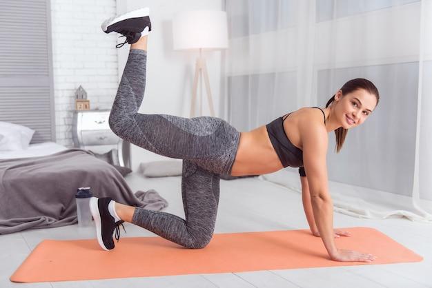 Adoro treinar. bela alegre atlética jovem de cabelos escuros sorrindo e fazendo exercícios para as pernas enquanto se exercita no tapete em casa