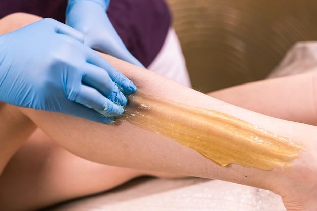 Adubar os cuidados da pele de depilação com açúcar líquido em close-up das pernas.