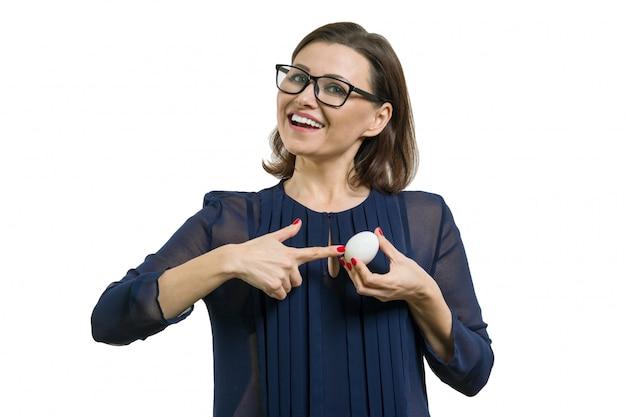 Adulta mulher atraente apontando para ovo branco