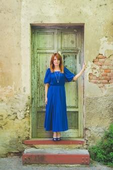 Adulta mulher bonita posando ao ar livre na porta da frente, olhando a câmera