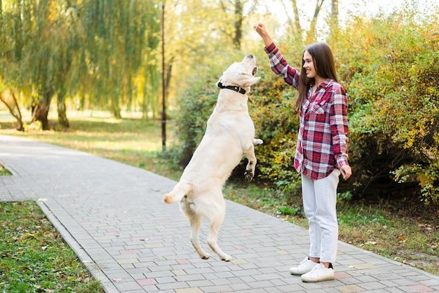 Adulta mulher brincando com seu cachorro