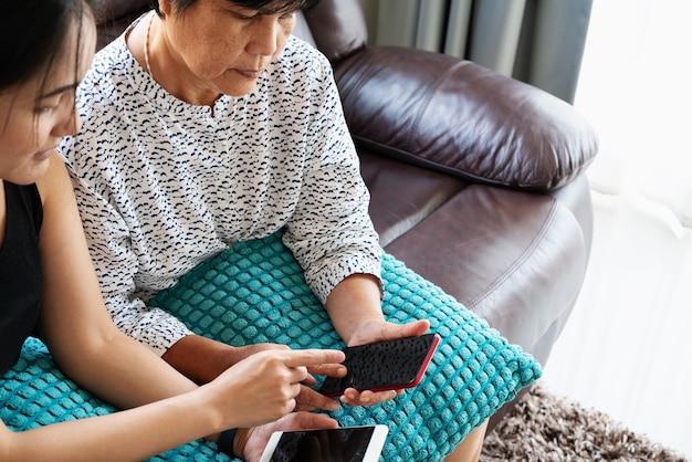 Adulta mulher e filha usando smartphone com tela em branco