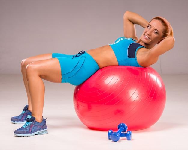 Adulta mulher está exercitando com bola de estabilidade e halteres.