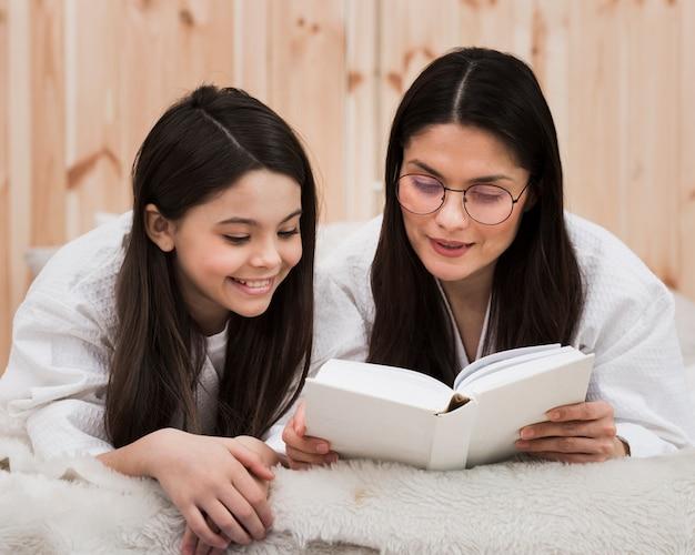 Adulta mulher lendo um livro com jovem