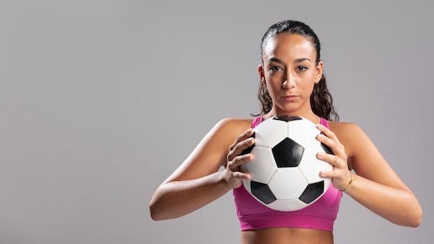 Adulta mulher segurando bola de futebol