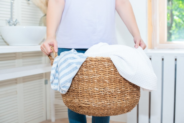 Adulta, velha, de cabelo escuro e curto, faz as tarefas domésticas. carrega roupas limpas em um cesto de roupa suja de vime e sorri.
