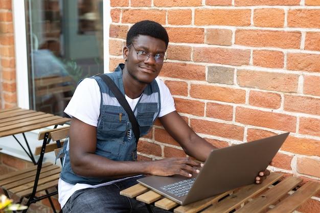Adulto africano masculino trabalhando com laptop contra o fundo da parede de tijolos