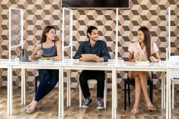 Adulto asiático comer fora juntos no novo restaurante normal