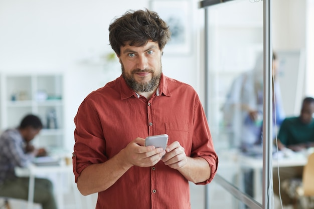 Adulto barbudo homem vestido com roupa casual e segurando o smartphone enquanto está no escritório