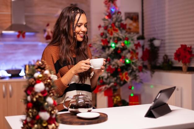 Adulto caucasiano segurando uma xícara de chá enquanto conversa online