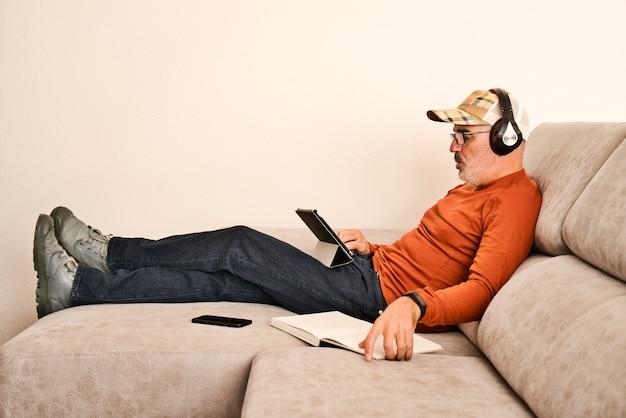 Adulto com óculos, barba curta e boné descansando no sofá cinza