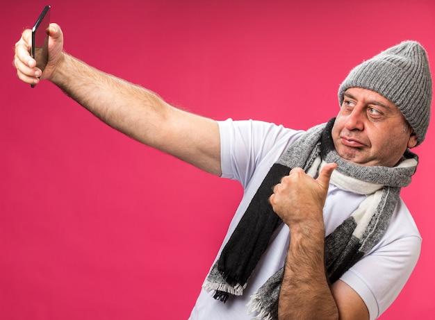 Adulto confiante, doente, caucasiano, homem, com, lenço, pescoço, usando, chapéu inverno, polegares para cima, olhando para, telefone, tomando selfie isolado na parede rosa com espaço de cópia