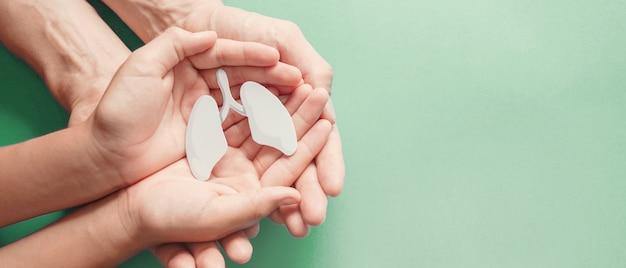 Adulto e criança mãos segurando um pulmão, dia mundial da tuberculose