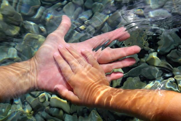 Adulto e crianças mãos segurando debaixo d'água