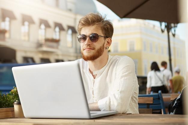 Adulto gengibre homem bonito com o computador portátil, sentado no terraço de um restaurante ou café
