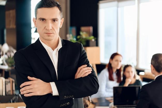 Adulto homem de jaqueta preta fica na frente do escritório do advogado