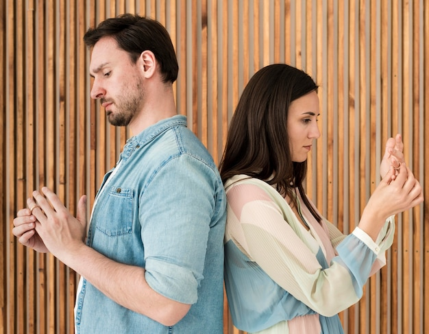 Adulto homem e mulher tirando alianças