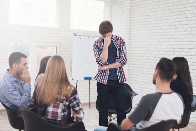 Adulto homem fica no círculo de pessoas durante a terapia de grupo.