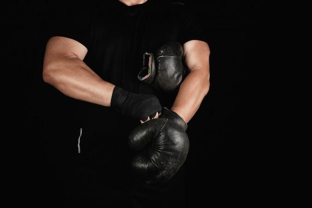 Adulto homem musculoso em roupas pretas coloca luvas de boxe pretas de couro