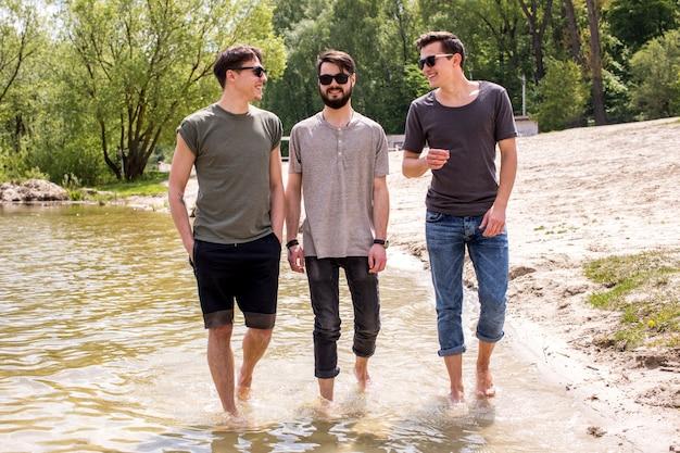 Adulto homens bonitos em pé na água perto da costa