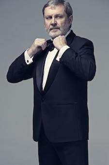 Adulto masculino envelhecido médio, vestindo um terno isolado na cinza