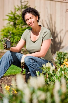 Adulto mid, mulher segura, planta, em, jardim, retrato