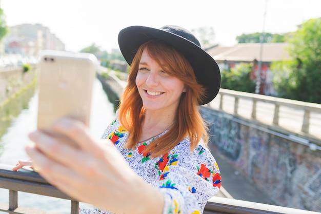 Adulto, mulher bonita, ao ar livre, luz traseira, usando, esperto, telefone, levando, selfie, sorrindo