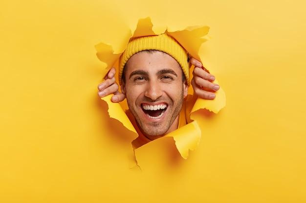 Adulto positivo do sexo masculino com barba por fazer parece feliz através do papel amarelo, mostra apenas o rosto