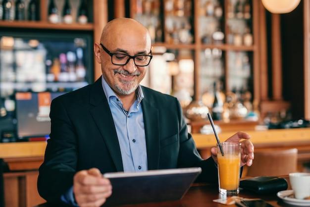 Adulto sênior barbudo de terno, bebendo suco e usando o tablet enquanto está sentado na lanchonete.