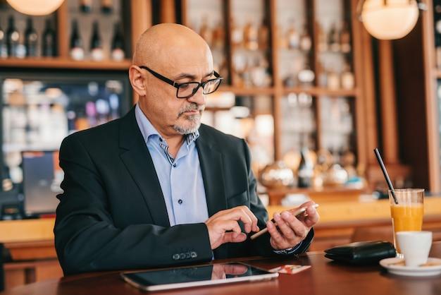 Adulto sênior barbudo de terno usando telefone inteligente para ler ou escrever mensagem enquanto está sentado na cafeteria.