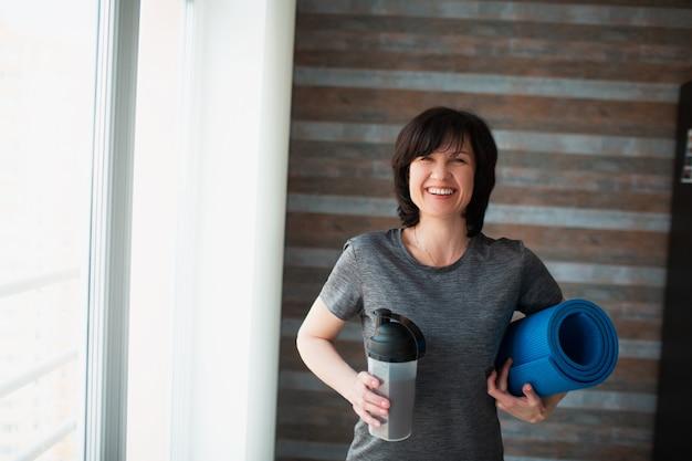 Adulto slim mulher tem treino em casa. fêmea sênior alegre positiva que olha na câmera e no sorriso. segurando o shake de proteína e o tapete de ioga nas mãos após o exercício. descanse e relaxe.