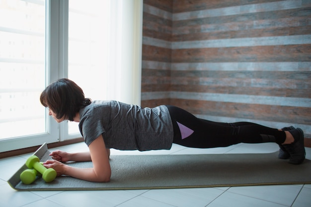 Adulto slim mulher tem treino em casa. fique na posição meia prancha e olhe para a frente. alongamento para trás e corpo inteiro. treinamento de mulher adulta magro bem construído.