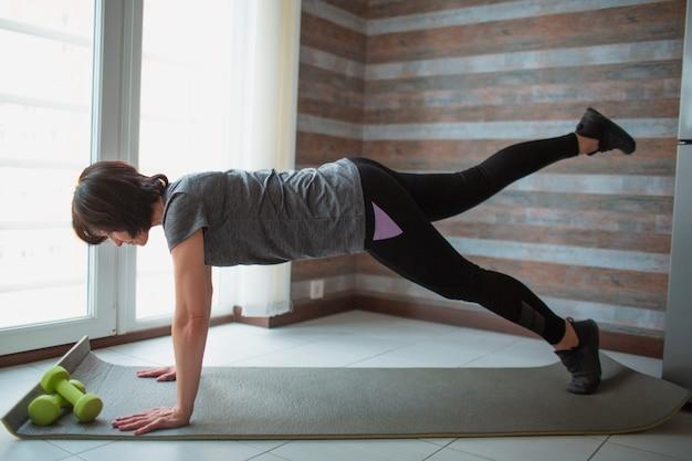 Adulto slim mulher tem treino em casa. modelo sênior forte e incrível bem construído fica em uma prancha de perna e treinamento.