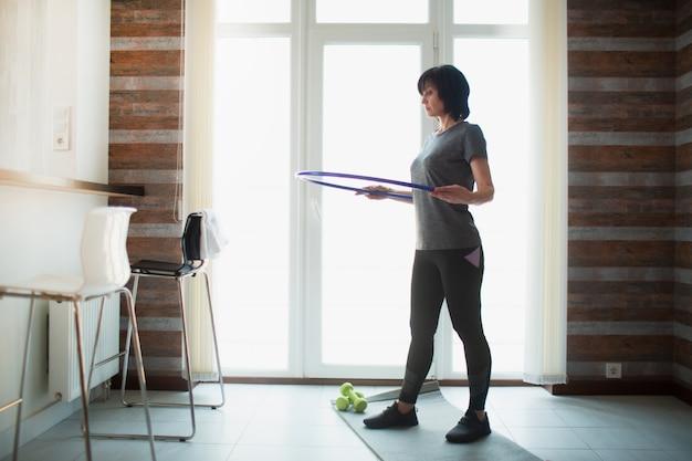 Adulto slim mulher tem treino em casa. o adulto sênior concentrado sênior que guarda o bambolê em torno da cintura e apronta-se para exercitar. tome cuidado com a boa forma e figura.